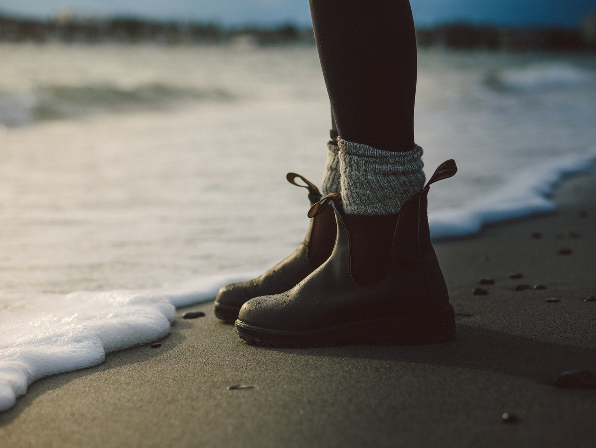 Picture of a woman's boots on the shoreline at the beach